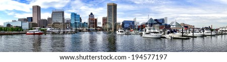 Baltimore Inner Harbor boat marina with shopping centers near National Aquarium and downtown business district buildings in scenic skyline of the Maryland city in wide cityscape panoramic view