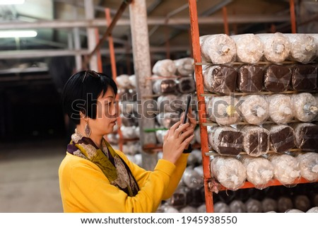 mature Asian woman take picture by cellphone mushroom farm in Puli township, Taiwan