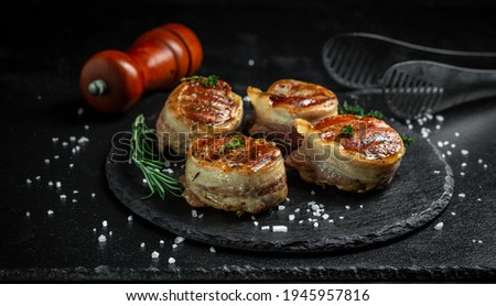 Grilled steak filet mignon wrapped bacon on dark concrete background. banner, menu recipe place for text, top view.