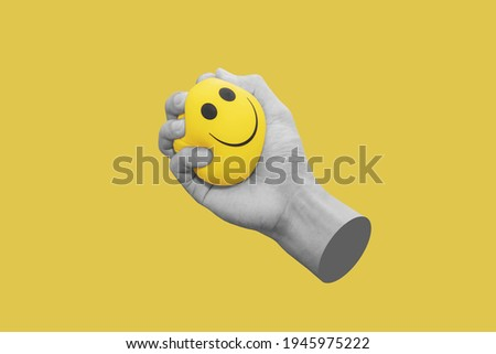 Hand squeeze yellow stress ball, isolated on yellow background