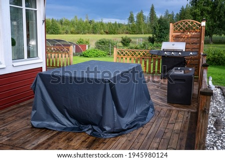Big table covered against of rain stands at wooden terrace. Red house, green garden, field and forest at background. Everything is very wet after heavy summer rain. Countryside, day time Royalty-Free Stock Photo #1945980124