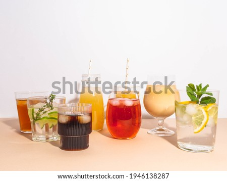 Various refreshing non-alcoholic drinks in glasses with ice. Different juice, homemade lemonade, iced coffee, iced fruit tea and smoothies on beige background. Copy space. Front view Royalty-Free Stock Photo #1946138287