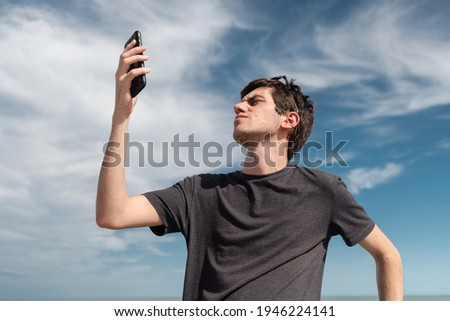 Low angle view of a young man searching for signal on his smartphone. Concept of connectivity and connection problems. Royalty-Free Stock Photo #1946224141