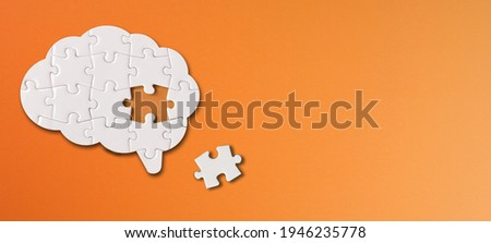 Brain shaped white jigsaw puzzle with copy space on orange background, a missing piece of the brain puzzle, mental health and problems with memory Royalty-Free Stock Photo #1946235778