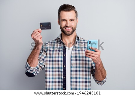 Photo portrait of cheerful man keeping mobile phone showing bank credit card isolated on grey color background