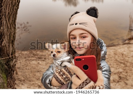 A teenage girl takes pictures of herself and the dog on a smartphone or speaks via video communication. Girl in a winter jacket and chihuahua. Girl on a background of a river with a dog. A pet.