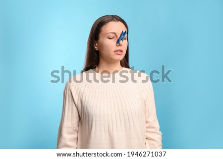 Young woman with clothespin on light blue background. Runny nose concept Royalty-Free Stock Photo #1946271037