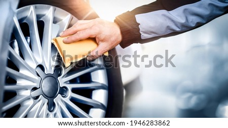 Worker washing car's alloy or alluminium wheels on a car wash. Rims detailing using cleaning yellow cloth. Royalty-Free Stock Photo #1946283862
