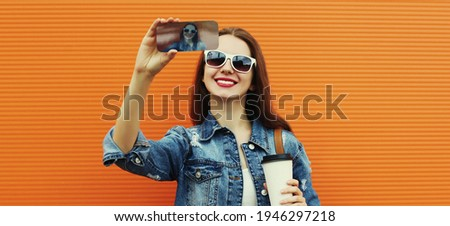 Portrait close up of smiling woman taking a selfie picture by smartphone wearing a denim jacket on an orange background