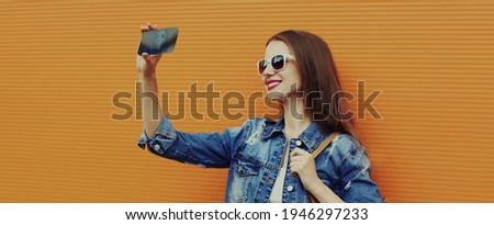 Portrait close up of smiling young woman taking a selfie picture by smartphone wearing a denim jacket on a orange background