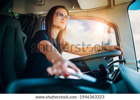 Portrait of beautiful young woman professional truck driver sitting and driving big truck. She is dangerously trying to take smart phone while driving. Royalty-Free Stock Photo #1946363323