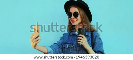 Portrait close up of stylish woman taking selfie picture by smartphone wearing a black hat, backpack on a blue background