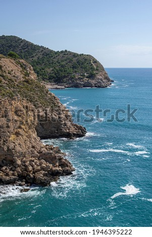 Beautiful Mediterranean coastline, pure blue, mountains with green trees, from the heights, waves crashing against the shore Royalty-Free Stock Photo #1946395222