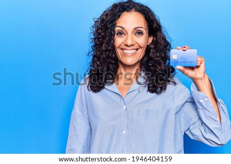 Middle age beautiful woman holding credit card looking positive and happy standing and smiling with a confident smile showing teeth