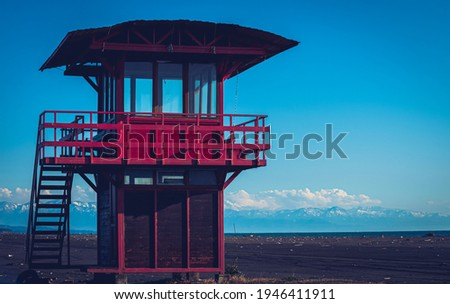 Red lifeguard rescue tower on the beach with blue sky background, Sea lifeguard tower. Desolate seascape. Royalty-Free Stock Photo #1946411911