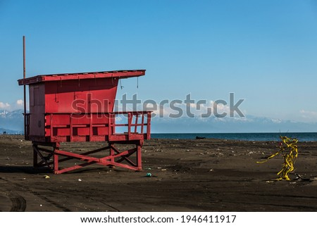 Red lifeguard rescue tower on the beach with blue sky background, Sea lifeguard tower. Desolate seascape. Royalty-Free Stock Photo #1946411917