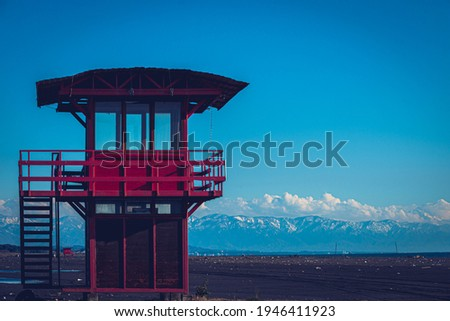 Red lifeguard rescue tower on the beach with blue sky background, Sea lifeguard tower. Desolate seascape. Royalty-Free Stock Photo #1946411923