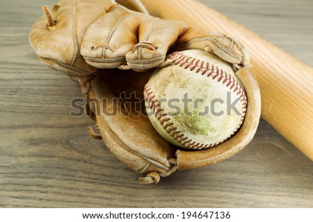 Closeup horizontal photo of an old dirty baseball inside of heavily used glove and wooden bat in background on rustic wood