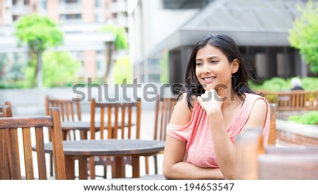 Closeup portrait, smiling, joyful, happy young woman, sitting, daydreaming nice things, isolated sunny outdoors, building background. Positive human emotions facial expressions feelings #194653547