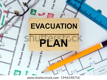 Wooden blocks with text Evacuation Plan Architectural design, sketch, drawing paper, drawings, simple pencil, eyeglasses with protractor on the table