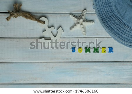 word summer in German is made up of volumetric colored letters on a light blue wooden background, white starfish, anchor concept of summer time, vacation time, travel, boat trip, beach impressions