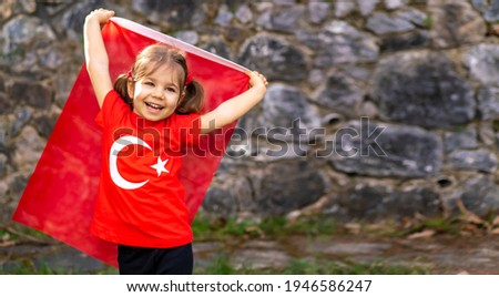 Portrait of happy little kid. Cute baby with Turkish flag t-shirt. Toddler hold Turkish flag in hand. Patriotic holiday. Adorable child celebrates national holidays. Copy space for text. Royalty-Free Stock Photo #1946586247