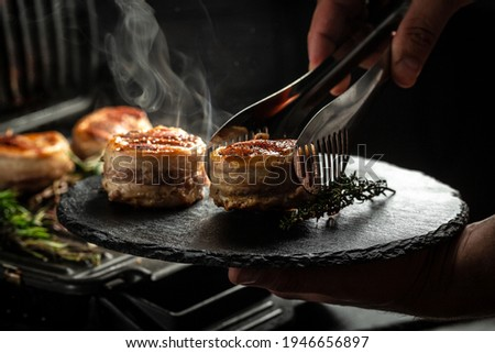 Medallions steaks from the beef tenderloin covered bacon on grill with smoke dark background. Cooking beef steak on grill by chef hands.