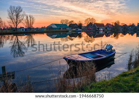 Boat on lake water at dawn village scene. Village lake boat sunrise dawn. Sunrise village lake boat at dawn landscape Royalty-Free Stock Photo #1946668750