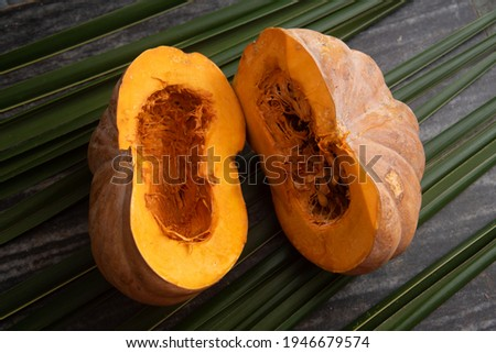 Fresh whole pumpkin vegetable cut in half , large raw ripe orange pumpkin sliced isolated on palm leaves. winter squash from farm harvested in Kerala India Royalty-Free Stock Photo #1946679574