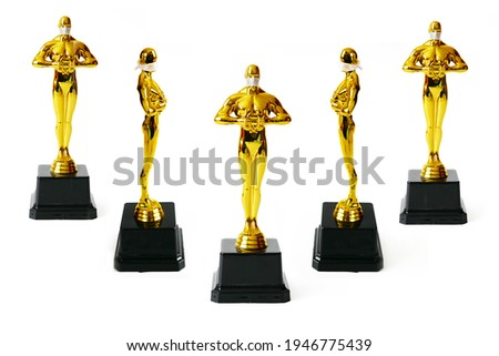 Hollywood Golden Oscar Academy award statue in medical mask isolated on white background. Set. Success and victory concept. Oscar ceremony in coronavirus time