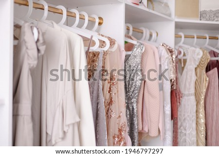 Beautiful female wardrobe. A lot of party dresses hanging on hangers in closet. Vintage clothing rental concept. Women's space. Large selection of various clothes. Small boutique showroom fashion shop Royalty-Free Stock Photo #1946797297