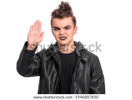 Teen boy with spooking make-up doing stop sign with palm of hand, isolated on white background. Teenager in style of punk goth dressed in black making stop gesture with serious facial expression