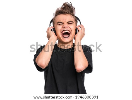 Teen boy in headphones with spooking make-up making Rock Gesture, isolated on white background. Teenager in style of punk goth dressed in black screaming and shouting