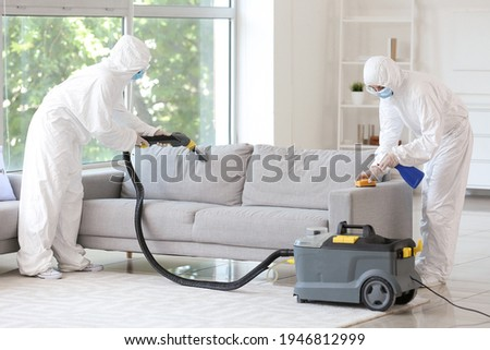 Workers in biohazard costume removing dirt from sofa in house Royalty-Free Stock Photo #1946812999