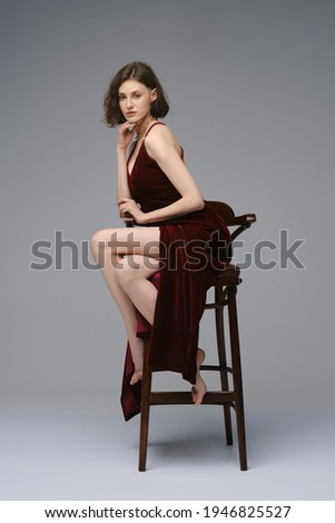 Full length portrait of barefoot young woman sits in profile on tall chair in dress with deep cut