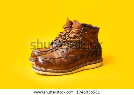 Dark Brown leather vintage boots on Yellow background, Vintage boots, Moc toe Royalty-Free Stock Photo #1946836561