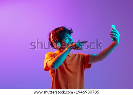Video call. Young man talking on phone isolated over pink-purple background in neon light. Future, gadgets, digital technology concept. Human emotion, facial expressions. Copy space for ad, design. Royalty-Free Stock Photo #1946930785