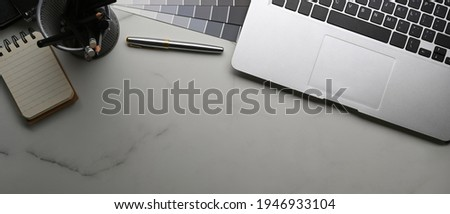 Above view of graphic designer workplace with laptop computer, color swatches, stationery and notebook on marble background.