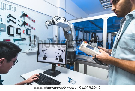 Meeting asian Engineers Maintenance Robot Arm at Lab. they are in a High Tech Research Laboratory with Modern Equipment.Professional Japanese Development Engineer is Testing an Artificial Intelligence Royalty-Free Stock Photo #1946984212