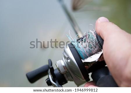 Fishing line tangled on lure Bait Casting Reel,like a Birds-nest tangles,Beginner fisherman. Royalty-Free Stock Photo #1946999812