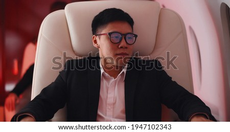 Young asian businessman shocked by plane flight in turbulent area. Portrait of stressed korean passenger sitting in leather seat at first class flying through turbulence area Royalty-Free Stock Photo #1947102343