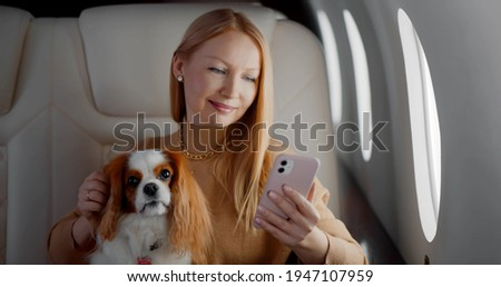 Beautiful rich woman with dog using smartphone in first class plane. Portrait of elegant wealthy lady stroking cocker spaniel and surfing internet on mobile phone in private jet Royalty-Free Stock Photo #1947107959