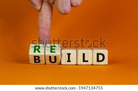 Rebuild symbol. Concept word 'rebuild' on wooden cubes on a beautiful orange table. Businessman hand. Orange background. Business and rebuild concept. Copy space. Royalty-Free Stock Photo #1947134755