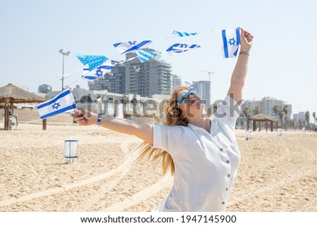 Girl with glasses with the Star of David with a garland of Israel flags on the seashore. Patriotic holiday Independence day Israel - Yom Ha'atzmaut concept. Royalty-Free Stock Photo #1947145900