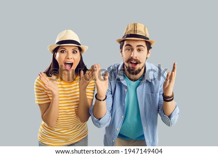 Close up portrait of a surprised married couple who found cheap plane tickets for vacation. Shocked man and woman with open mouth screaming with pleasure on a gray background. Banner. Place for text.