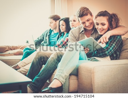 Group of students with tablet pc and laptop preparing for exams in apartment interior  #194715104