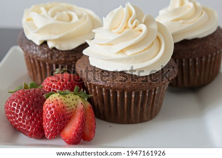 Chocolate cupcakes with vanilla buttercream icing and strawberry's to the side.