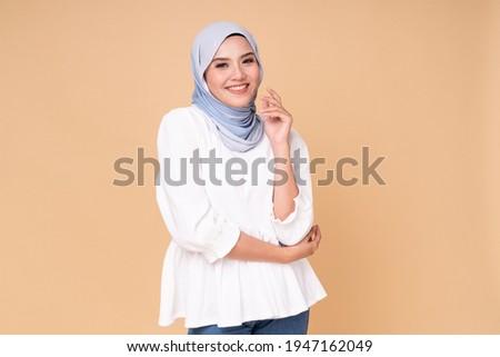 Portrait of hijab girl smiling. Pretty muslim girl. Beautiful asian muslimah woman model posing on beige background studio. Royalty-Free Stock Photo #1947162049