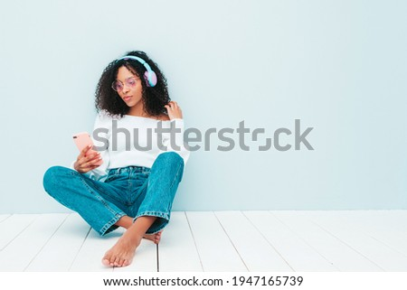 Beautiful black woman with afro curls hairstyle.Smiling model in sweater and jeans.Sexy carefree female listening music in wireless headphones.Sitting in studio near light blue wall. Holds smartphone