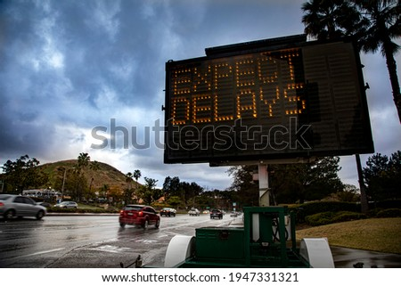 Electronic digital traffic control sign stating Expect Delays with blurred traffic driving on wet streets